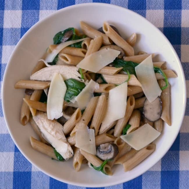 One Pot Creamy Chicken Mushroom Pasta on a white plate on a blue and white checkered cloth