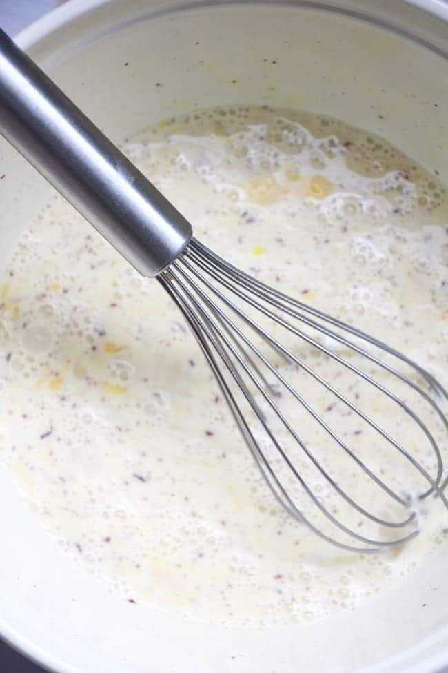 milk, cream, cinnamon, vanilla and eggs being whisked together in a large bowl