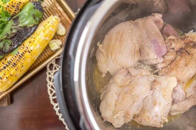 chicken being cooked in an instant pot next to a basket of grilled corn and peppers