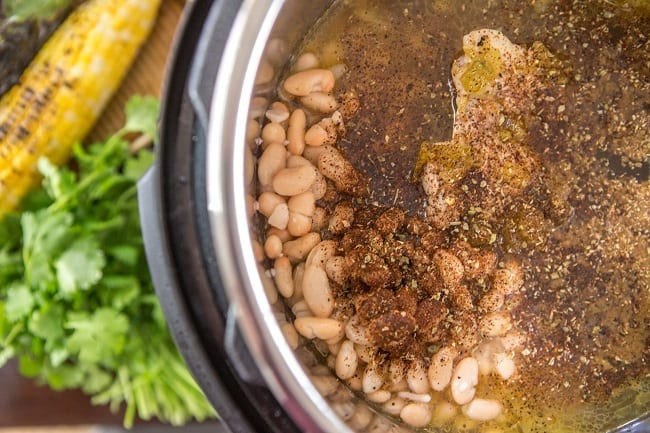 chicken, beans, seasoning, and broth in an instant pot next to some vegetables and garnish