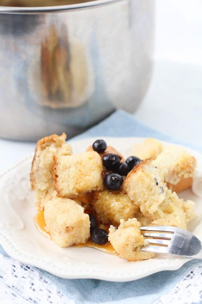 french toast casserole on a white plate topped with blueberries with a fork in one of the pieces with an instant pot bowl in the background