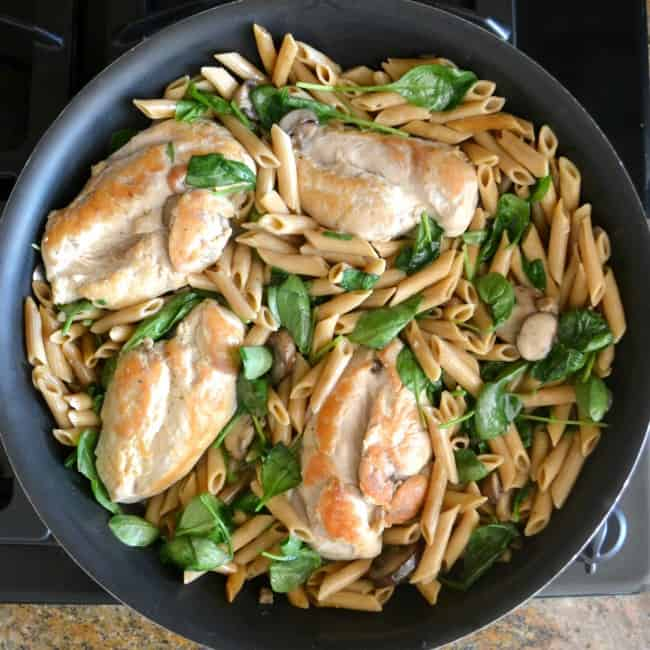 chicken, mushrooms, chicken broth, milk, whole wheat pasta, spinach and seasoning being cooked in a pan