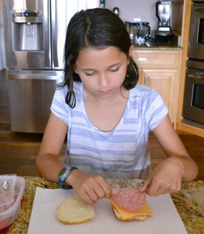 a girl making her sandwich in the kitchen