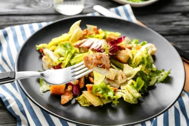 a fork holding some salad topped with rotisserie chicken above the salad on a black plate on a striped cloth on a brown table