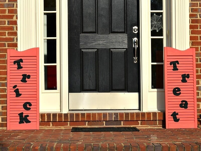 orange shutters with the words Trick Treat on them on a front porch