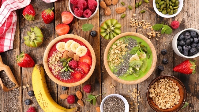 bowls of fruit and smoothie bowls on a table with lots several different fruits on it