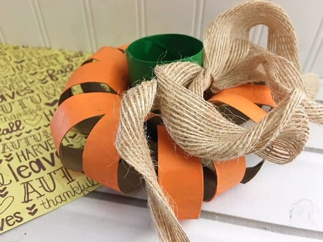 a DIY toilet paper roll pumpkin with a burlap ribbon on it