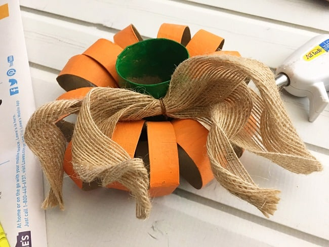 orange cardboard rings with a green toilet paper roll in the center next to a burlap ribbon on a white wood background