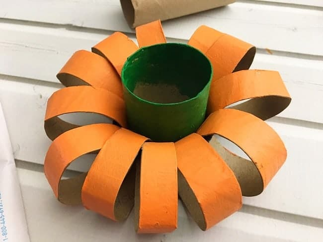 orange cardboard rings with a green toilet paper roll in the center on a white wood background