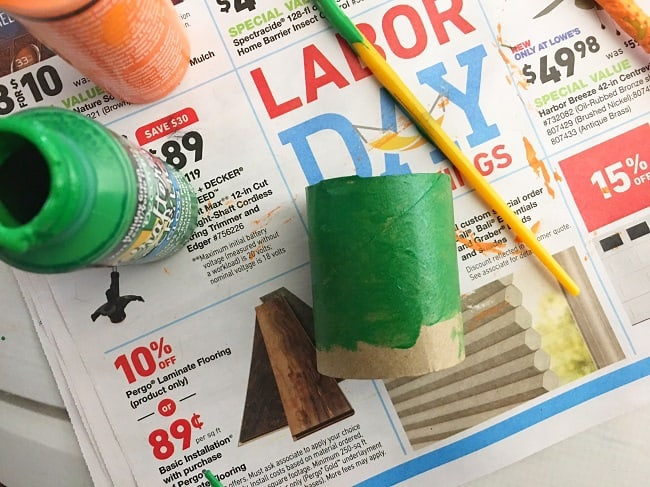 a toilet paper roll partially painted green, next to a paintbrush and bottles of green and orange paint, on a newspaper ad