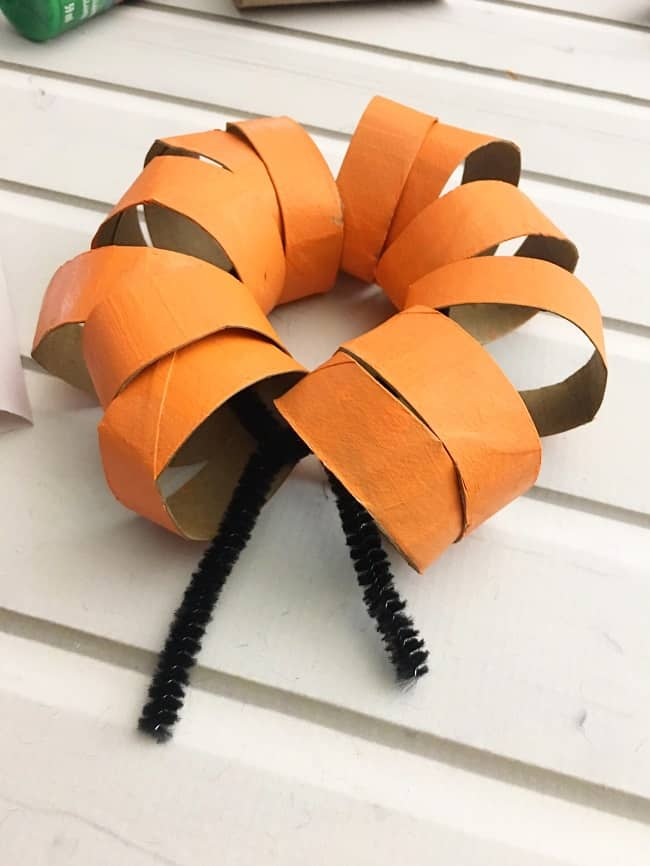 orange cardboard rings on a black pipe cleaner on a white wood background