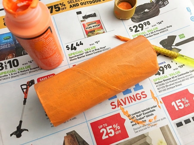 a toilet paper roll painted orange, next to a paintbrush and bottle of orange paint, on a newspaper ad
