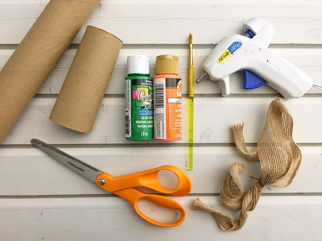 "Paper towel roll, toilet paper roll, Orange and green craft paint,  1"" burlap ribbon, Paint brush, Scissors, hot glue gun all on a white wood background"