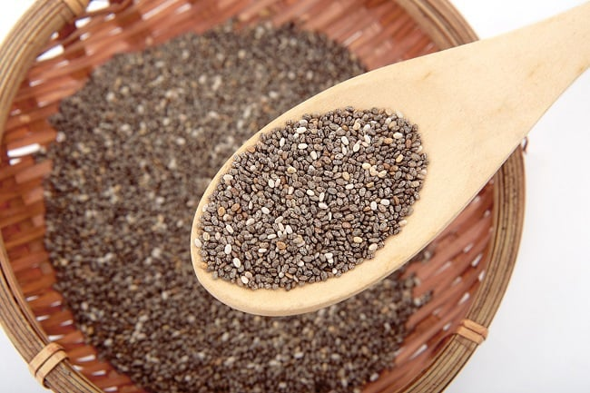 a wooden spoon with chia seeds on it above a wicker basket with chia seeds in it