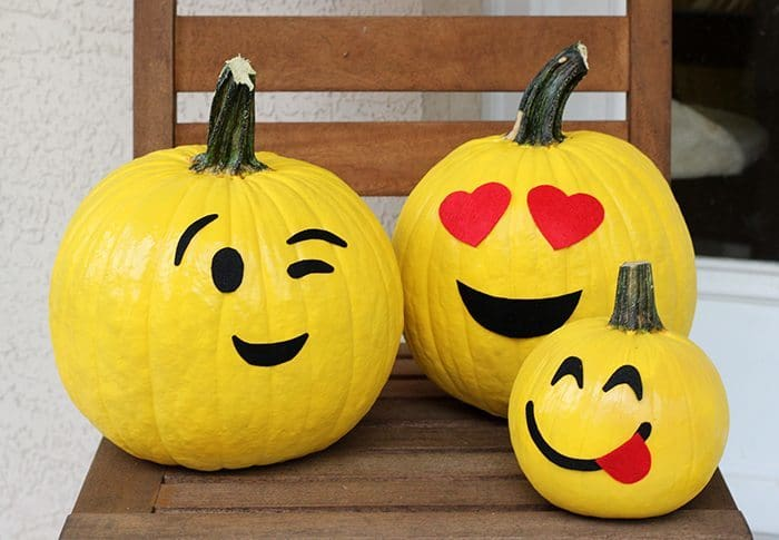pumpkins decorated to look like emojis on a brown chair