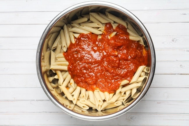 cooked pasta and sauce in an instant pot on a white wood background