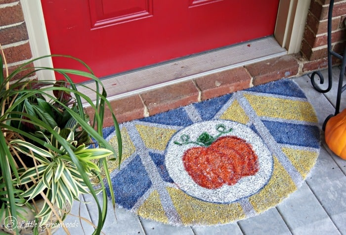 a pumpkin front porch mat next to a plant and a pumpkin with a red door in the background