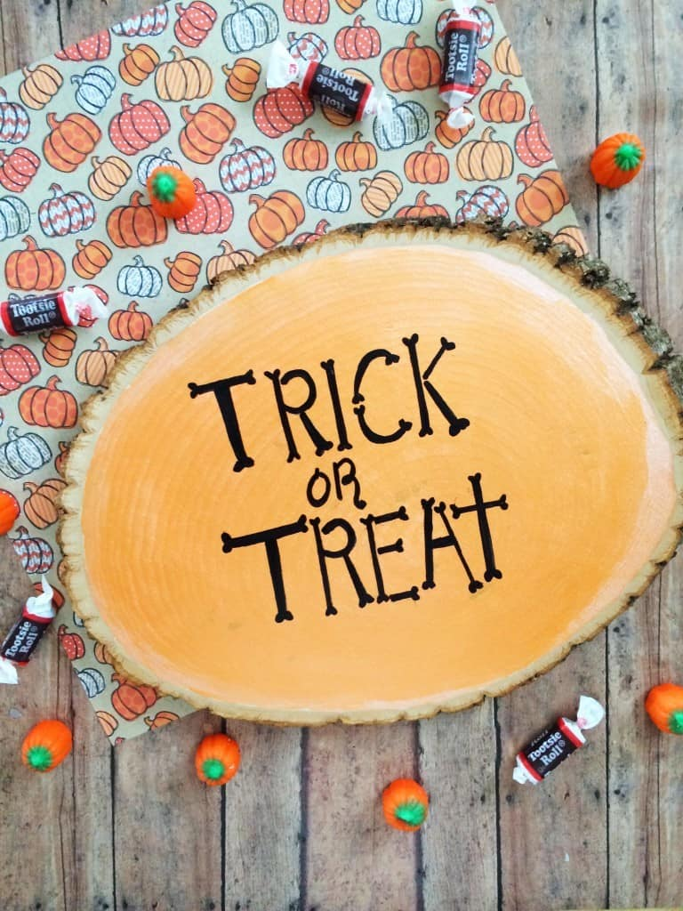 a tree stump decorated with the words Trick or Treat next to candy on a pumpkin cloth on a brown wood background