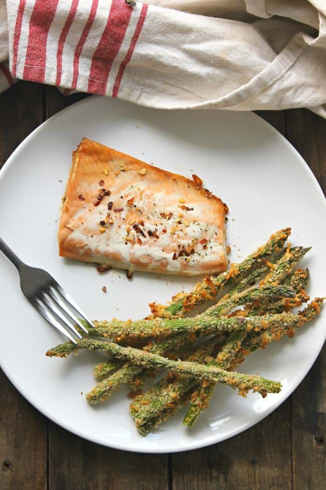parmesan asparagus fries and salmon next to a fork on a white plate on a brown table next to a white and red striped cloth