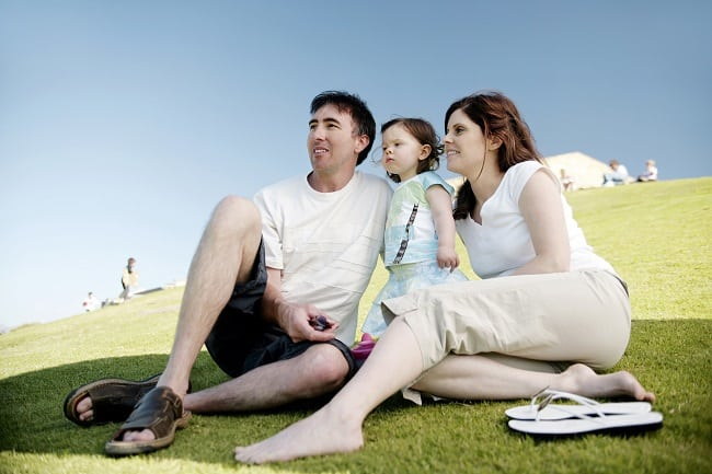 a mom, dad, and little girl sitting on a grassy hill