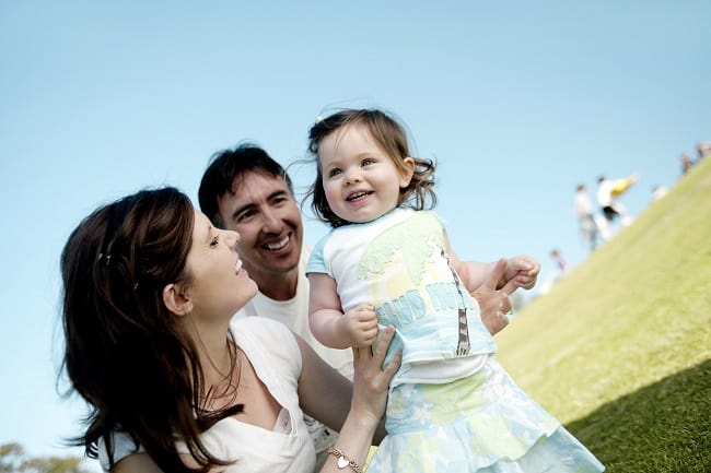 a mom, dad, and little girl playing on a grassy hill