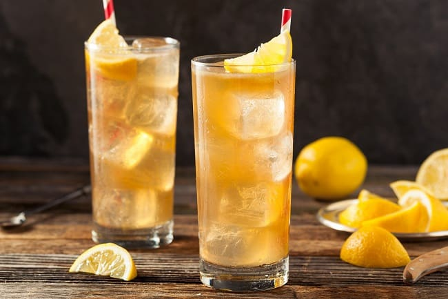 a dark and stormy rum drink in two glasses topped with a lemon wedge on a brown table with more lemon wedges and a lemon on the table