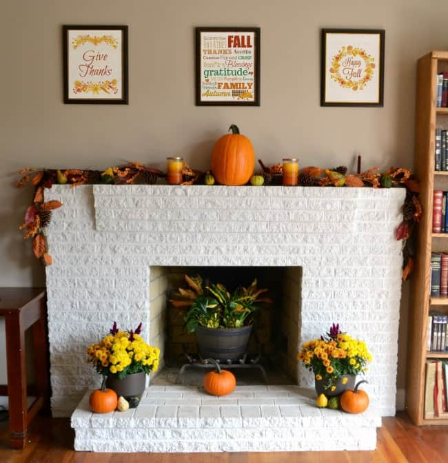 a white brick fireplace mantle and the wall behind it decorated for fall with pumpkins, flowers, leaves and pictures