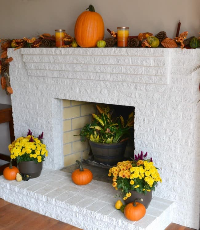 pumpkin, gourds, pinecones, leaves, candle, pots with yellow flowers, and a plant, on a white brick fireplace mantel