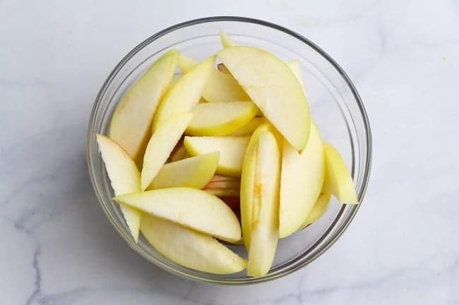 sliced apples in a glass bowl on a white counter