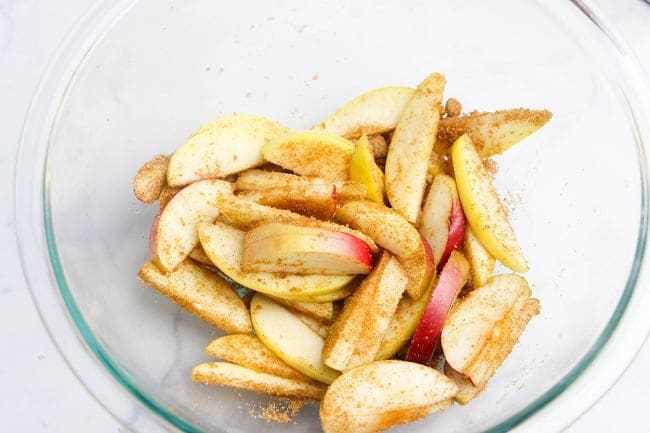sliced apples coated with brown sugar and cinnamon in a glass bowl on a white counter