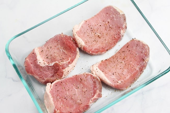 raw pork chops seasoned with salt and pepper in a glass dish on a white counter
