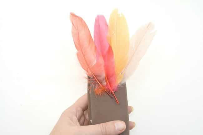 a hand holding a juice box wrapped in brown craft foam with fake feathers glued near the top