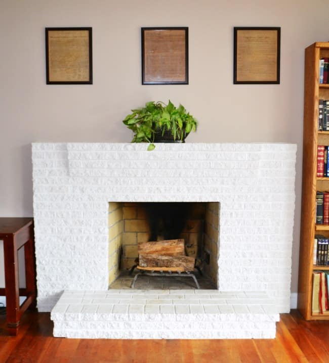 a white brick fireplace with a plant on top and a wall with frames on it in the background