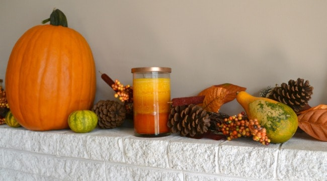 pumpkin, gourds, pinecones, leaves, candle on a white brick fireplace mantel
