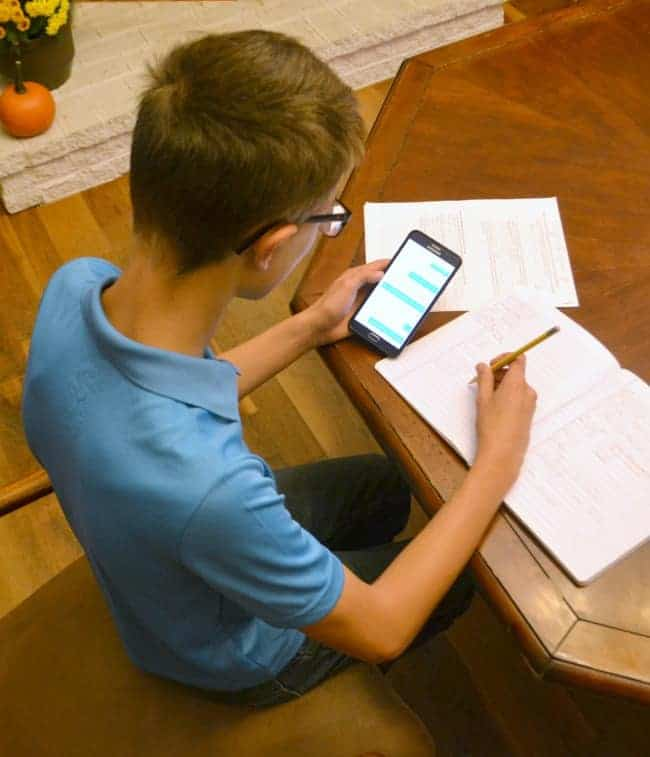 an overhead view of a young man sitting at a table getting on demand homework help from the yup app on his phone