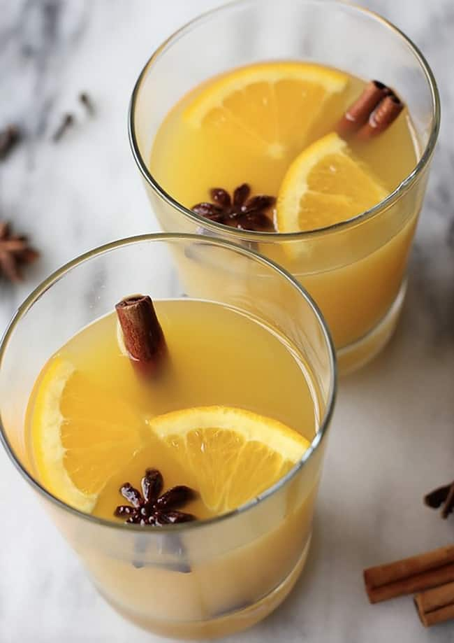 orange cinnamon blossom wine in two glasses with a cinnamon stick and orange wedges in them