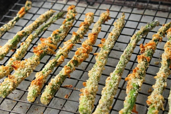 parmesan asparagus fries on a wire rack on a baking pan