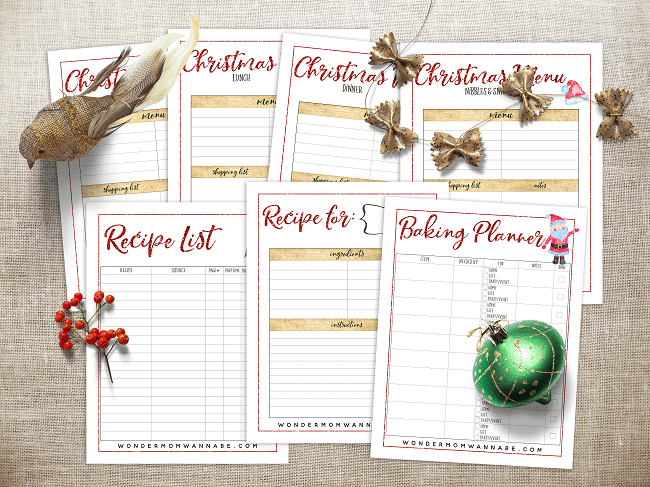 printable Christmas menu planning pages with a fake bird, gold bows, fake holly berry and a green ornament on top of the pages, all on a brown background