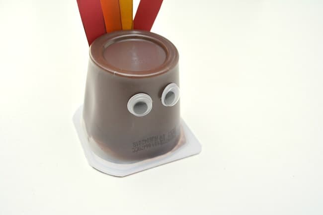 an upside down pudding cup with red, yellow and orange paper feathers and googly eyes on it