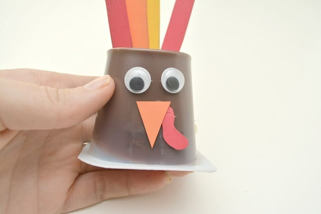 a hand holding an upside down pudding cup decorated with googly eyes, an orange paper beak with a red waddle, orange paper feet and red, orange and yellow paper feathers to look like a turkey, all on a white background