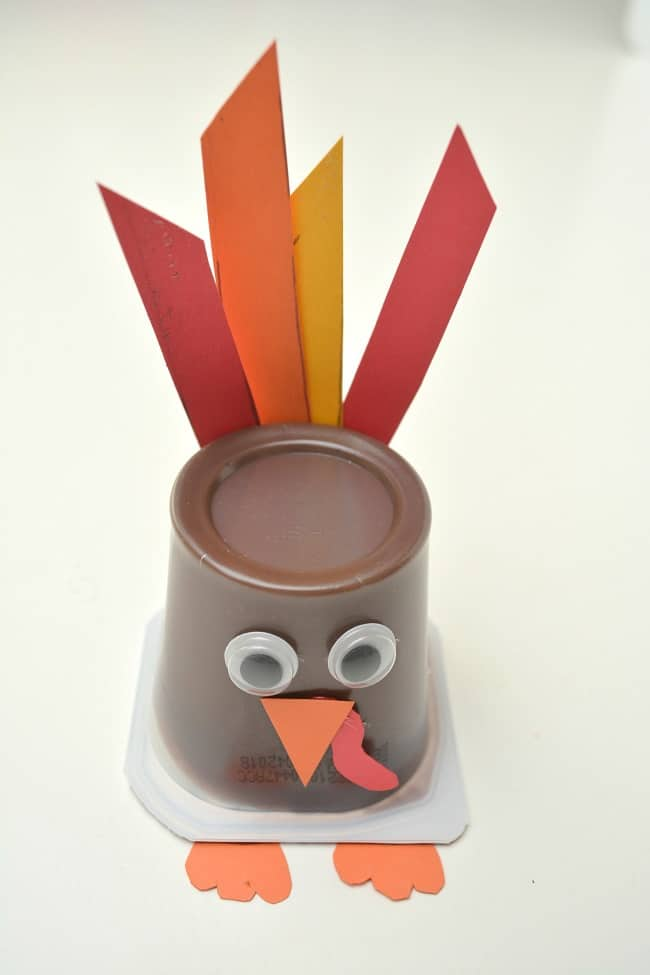 a pudding cup decorated with an orange beak and red wattle, googly eyes, orange feet and red, orange and yellow feathers to look like a turkey