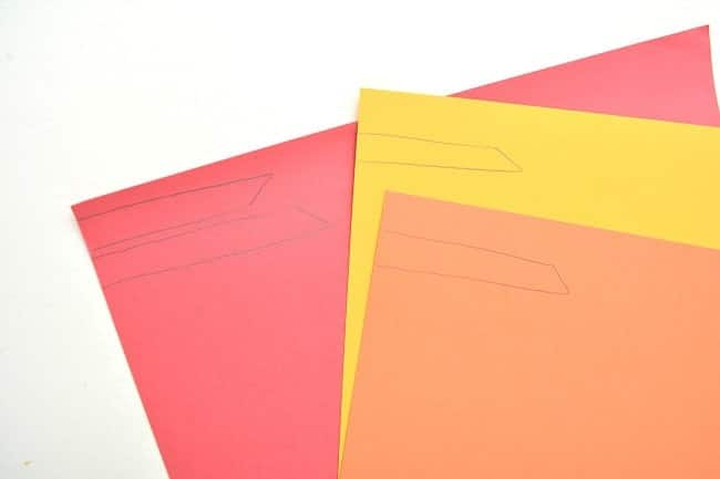 red, yellow and orange paper with feathers drawn on them with a pencil