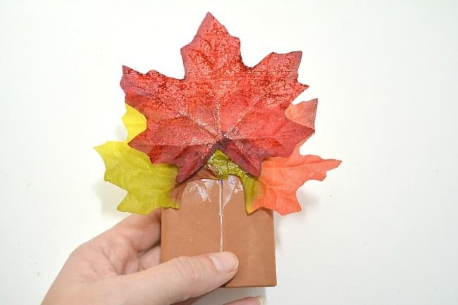 a hand holding a raisin box wrapped in brown cardstock with fake leaves glued to it, on a white background