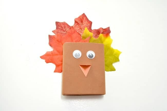 a raisin box decorated with brown paper, orange paper beak, googly eyes, and fake leaves to look like a turkey