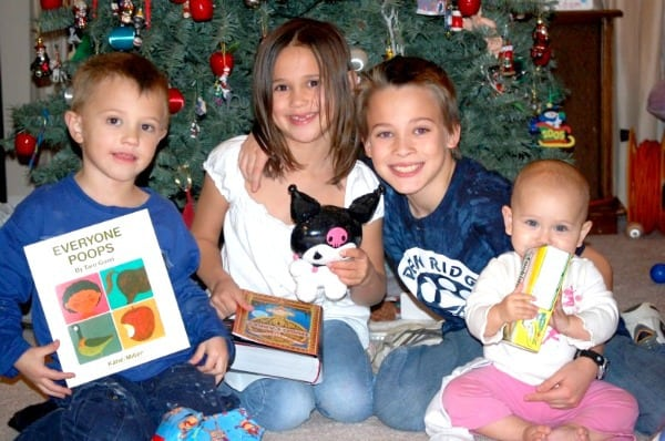 four kids holding their Christmas presents in front of the Christmas tree