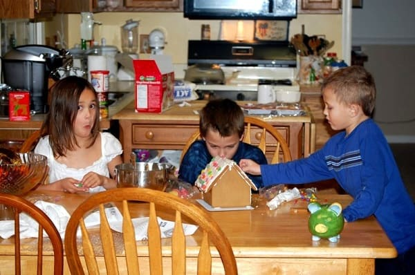 three kids sitting at a kitchen table making gingerbread houses