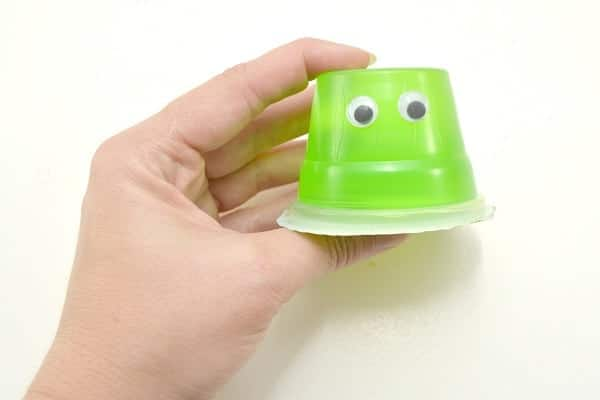 a hand holding an upside down green jello cup with google eyes on it on a white background