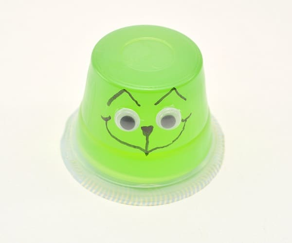 an upside down green jello cup with google eyes on it and a face drawn on with a black sharpie on a white background