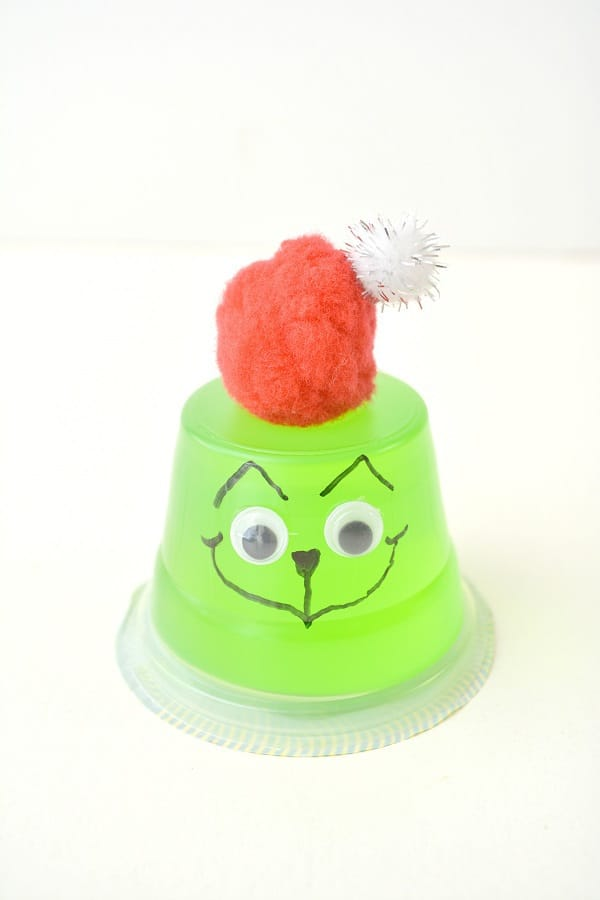 an upside down green jello cup with google eyes on it, a face drawn on with a black sharpie, topped with a red and white pom pom to look like the grinch on a white background