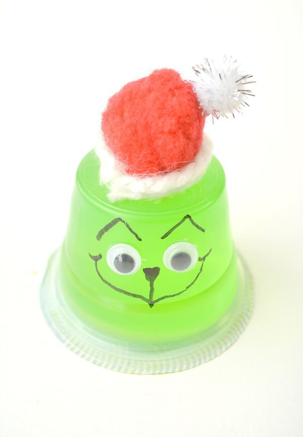 an upside down green jello cup with google eyes on it, a face drawn on with a black sharpie, topped with a red and white pom pom wrapped in white yarn to look like the grinch on a white background
